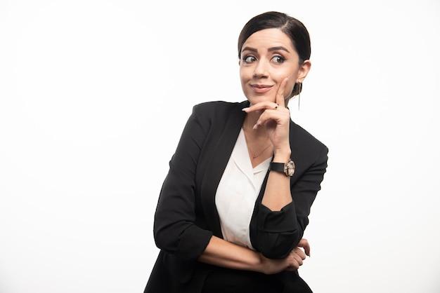 Donna di affari che posa in vestito su una priorità bassa bianca. foto di alta qualità