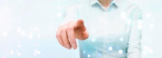 Деловая женщина нажимает на сенсорный прозрачный экран рукой. вид спереди. светло-голубой фон