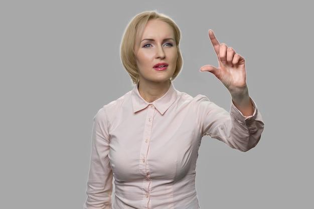 目に見えない仮想画面を押してスワイプするビジネスウーマン。仮想画面上のアイコンを指でズームする魅力的な女性。将来のタッチスクリーン技術と人々の概念。