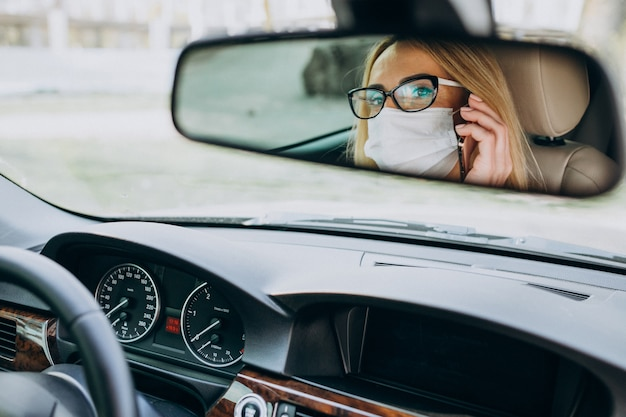 Donna di affari nella maschera di protezione che si siede dentro un'automobile
