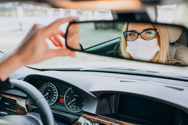 Business woman in protection mask sitting inside a car