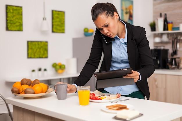 Деловая женщина читает плохие новости на своем планшете во время завтрака