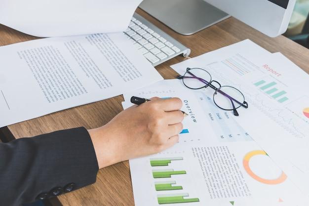 Деловая женщина, чтение и проверка графических документов на своем столе, бизнес-концепция