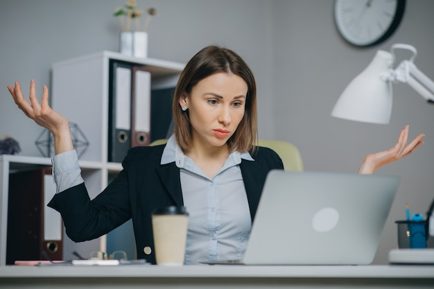 Business woman reading bad news on laptop computer at coworking space. upset woman closing down laptop in office. tired woman breathing deep at workplace.