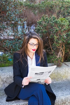 Business woman reading newspaper outside