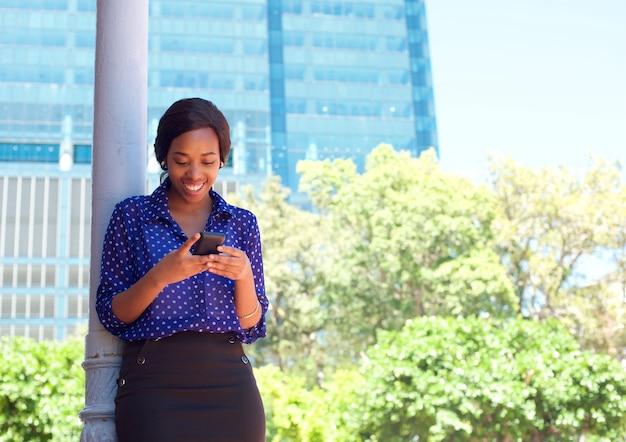 휴대 전화 야외에서 문자 메시지를 읽고 비즈니스 우먼