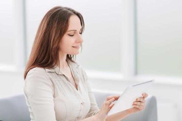 디지털 태블릿에서 텍스트를 읽는 젊은 비즈니스 우먼. 사람과 기술