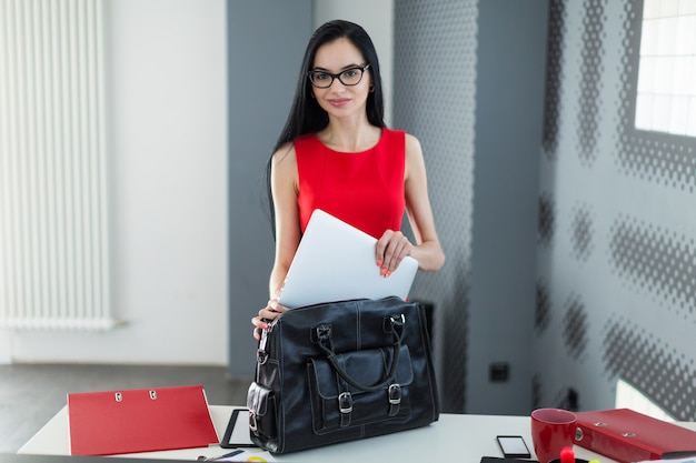 Business woman in a red dress folds the paper in the bag