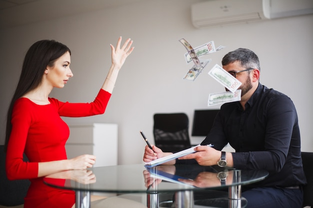 Business woman in red dress throws money to businessman