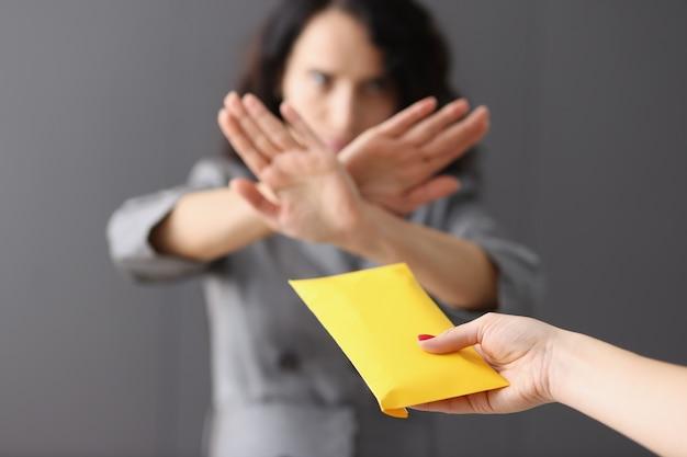 비즈니스 여성은 노란색 봉투 부패와 뇌물수수 개념으로 돈을 거부합니다.