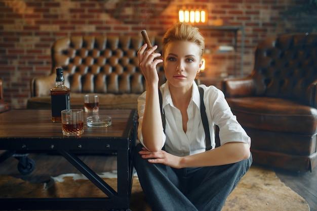 ビジネスの女性は、ウイスキーと葉巻でリラックスします。