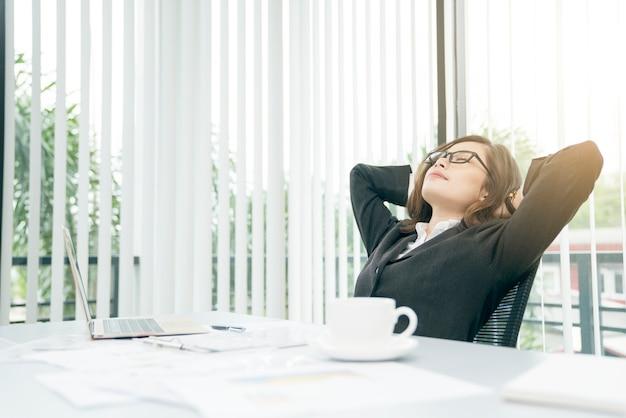 ビジネスの女性は彼女の頭の後ろに手でリラックスし、仕事から疲れた後にオフィスチェアに座って