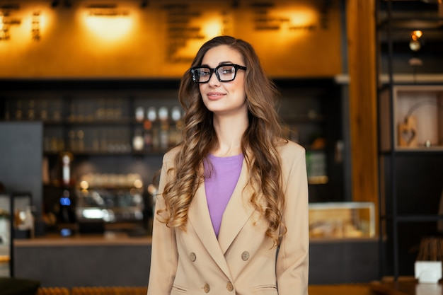 Business woman restaurant owner dressed elegant pantsuit standing in restaurant with bar counter background caucasian female glasses business person indoor