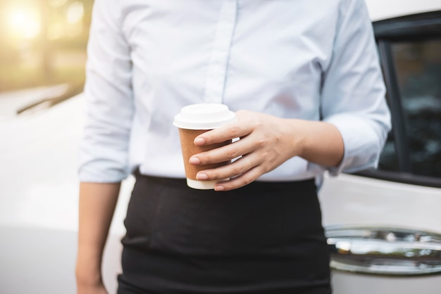 奪うためにコーヒーカップを持っているビジネス女性の手