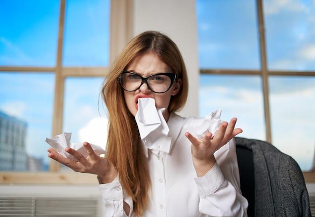 ビジネスウーマン秘書は、オフィスの不満の感情の手で紙をコインします。高品質の写真