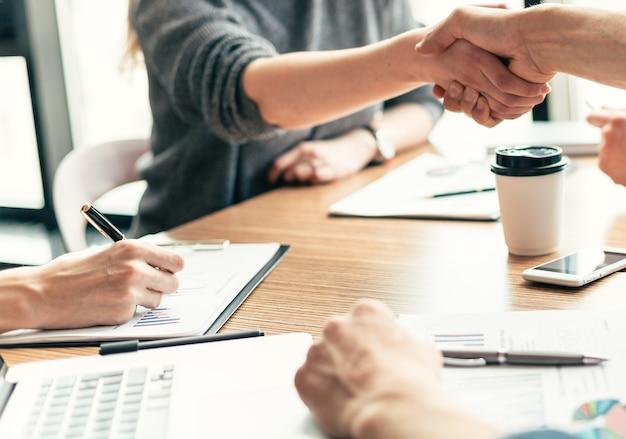 同僚と握手するビジネスウーマン