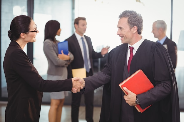 Business woman shaking hands with lawyer