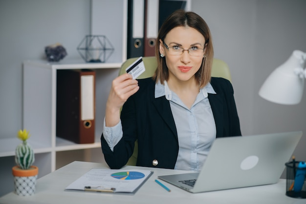 Business woman shopping online with laptop in office. young woman hold bank credit card in hand and buying from computer