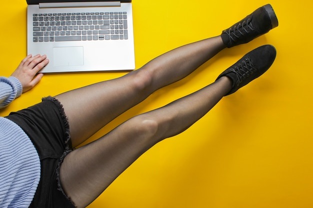 Business woman in shorts, tights and boots is typing on a laptop while sitting on a yellow floor. freelance, blogger, online worker concept