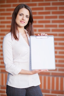 Business woman showing blank clipboard at her office