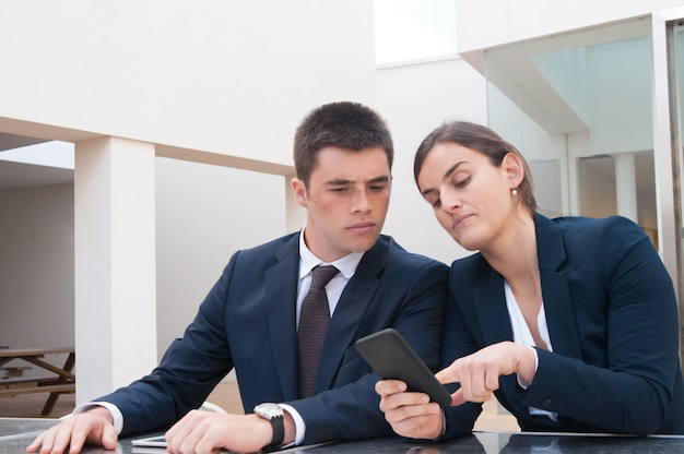 Business woman showing information on phone screen to coworker