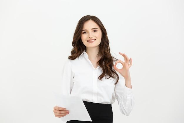 ビジネスの女の子が幸せに笑顔ok手のサインを表示