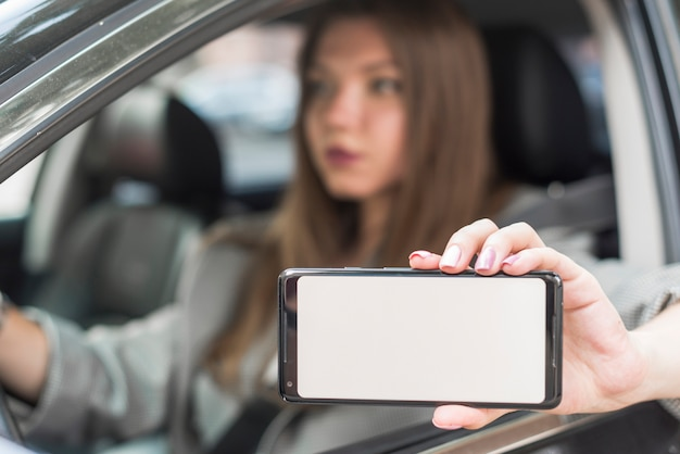Business woman showing a smartphone in the car