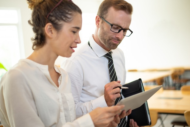 Business woman showing something on tablet screen to thoughtful male colleague.