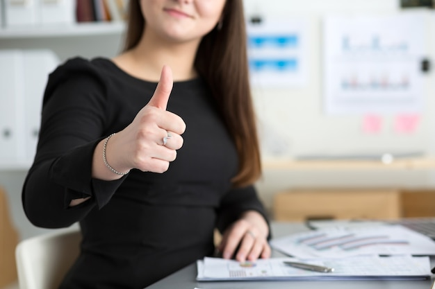 Business woman shows thumb up sitting at her office closeup. perfect goods or service quality concept. satisfied customer. okay symbol
