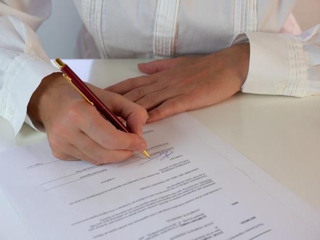 Деловая женщина, подписывающая официальный документ или контракт. сосредоточьтесь на подписи