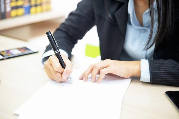 ビジネスの女性が文書に署名します。取引コンセプト。
