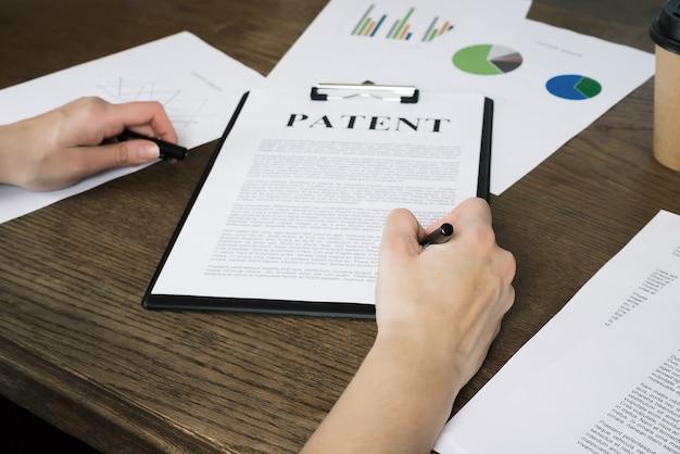 ビジネスウーマンが特許に署名知的財産保護の概念