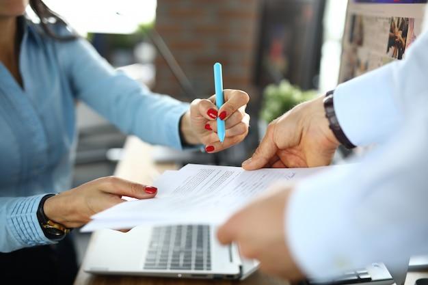 ビジネスの女性がオフィスのクローズアップで契約に署名します。