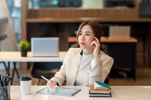 비즈니스 우먼 앉아서 사무실에서 태블릿을 사용 하여 작업 계획에 대해 생각합니다.