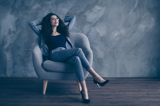 Business woman sit in chair enjoying free time over gray wall
