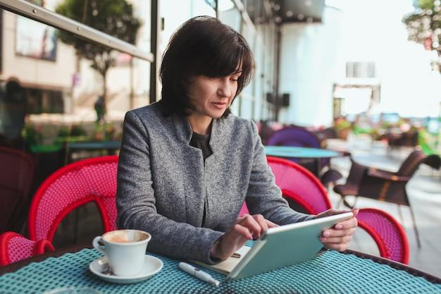 ビジネスの女性が座っているし、現代のタブレットを使用して一人で働く