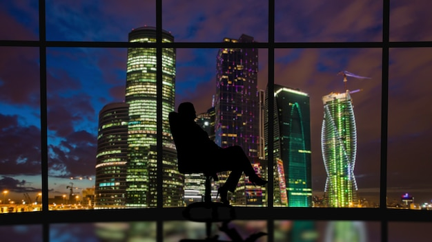 The business woman sits in the office near the windows with a night city view
