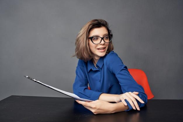 Деловая женщина, сидящая за своим столом, документы офисной самоуверенности