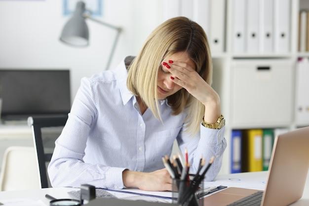 オフィスのテーブルに座って、従業員の概念の彼女の頭の過労を保持しているビジネス女性