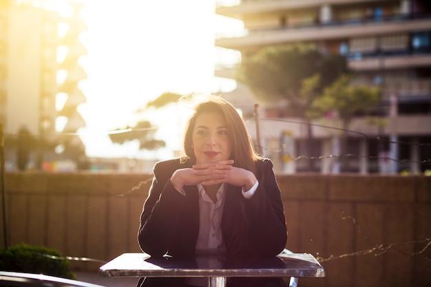 外のテーブルに座っている女性実業家