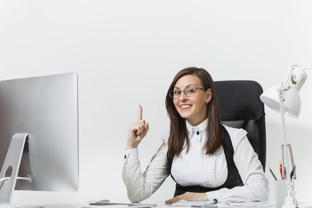 책상에 앉아 있는 비즈니스 여성, 가벼운 사무실에서 문서와 함께 현대적인 컴퓨터에서 작업, 검지 손가락으로 거꾸로 가리키는