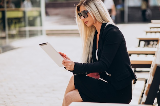Business woman sitting on bench and working on tablet