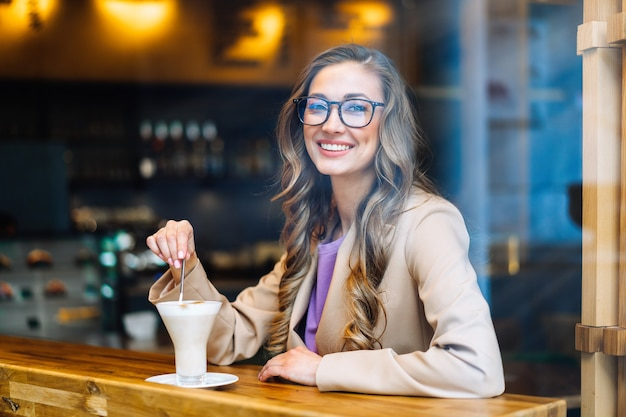 Business woman sitting cafe behind window waiting business partner caucasian female resting cafeteria drink late coffee smile looking outside