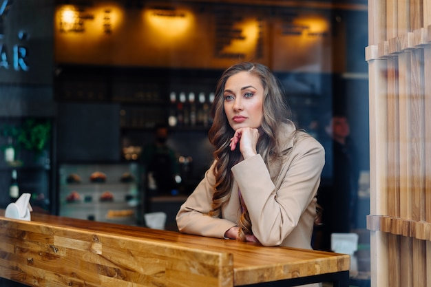 Business woman sitting cafe behind window waiting business partner caucasian female resting cafeteria drink late coffee