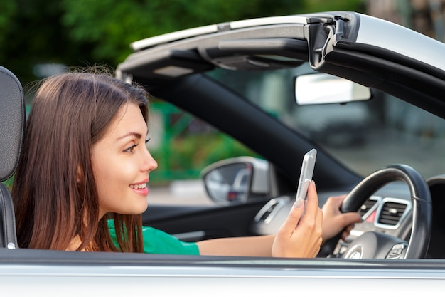 Business woman sitting in car and using her smartphone.