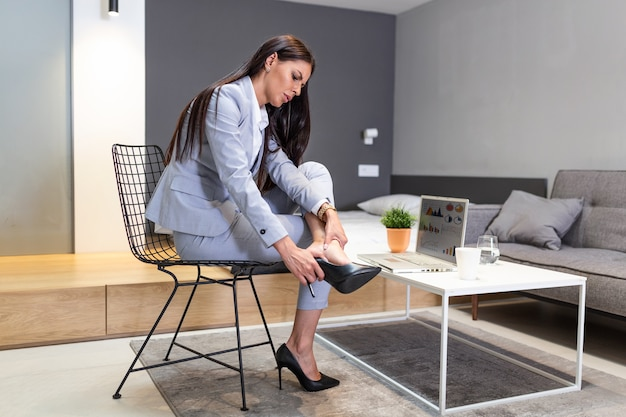Business woman sitting in chair, hold legs has pain varicose veins symptom from  high heels.