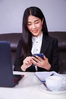 Business woman sitting at the desk and using mobile phone