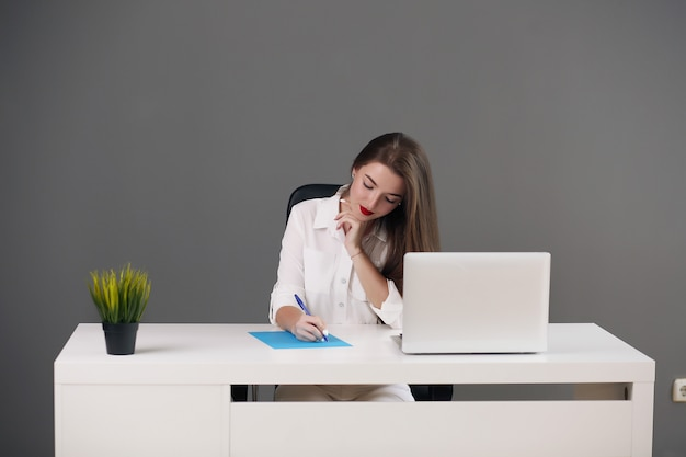 Business woman sitting at a desk with a laptop and looking away in the office