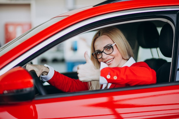 車のショールームで新しい車に座っている女性実業家