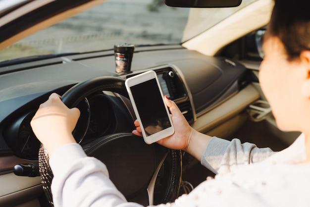차에 앉아서 스마트폰을 사용하는 비즈니스 우먼. 여성 운전자와 전화 화면이 있는 모형 이미지